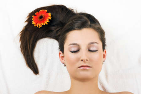 young beautiful woman in a spa with a flower photo