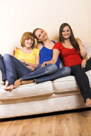 Three young beautiful women are sitting on their lounge photo