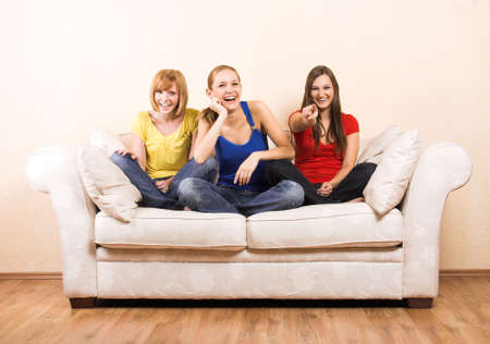 Three young beautiful women are laughing on a lounge photo