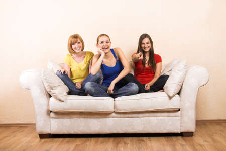 Three young beautiful women are laughing on a lounge