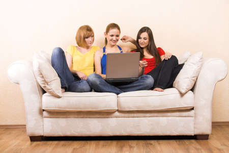 jubilate: Three young beautiful women are sitting on a lounge with a laptop