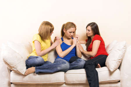 a young woman is having problems and is comfort by her girlfriends Stock Photo