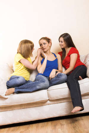 a young woman is having problems and is comfort by her girlfriends photo