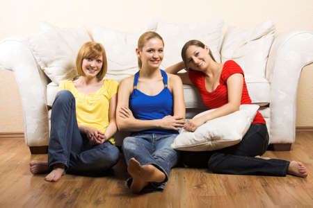 Three young beautiful women are sitting in front of their sofa photo