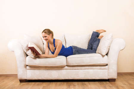 a young beautiful woman is reading on a lounge photo