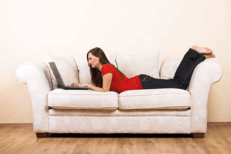 a young beautiful woman with a laptop on a lounge photo