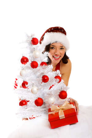 smiling christmas woman isolated on white background with a gift and a tree photo