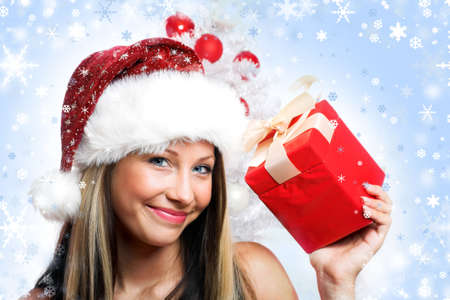 smiling christmas woman with a christmas-tree and a gift photo