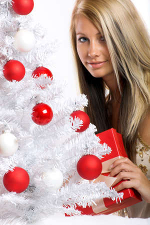 smiling christmas woman owith a christmas-tree and a gift photo