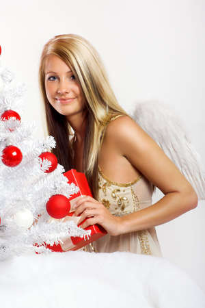 smiling christmas angel on white background with a christmas-tree and a gift photo