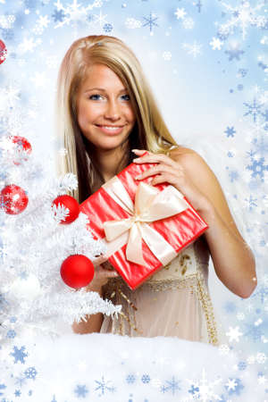 smiling christmas angel isolated on white background with a christmas-tree and a gift photo