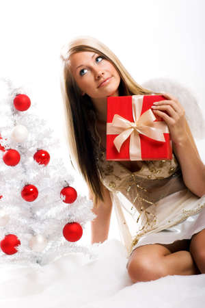 smiling christmas angel on white background with a christmas-tree and a gift Stock Photo - 5017888