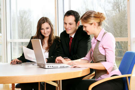 a successful business team is working on a table with documents and a laptop Stock Photo