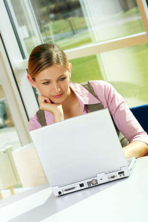 a successful business woman is working on a table with a laptop
