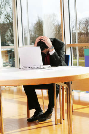 a business man is frustrated on a table with a laptop