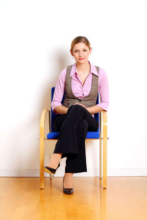portrait of a successful young woman sitting on a chair Stock Photo