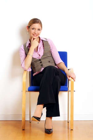 portrait of a successful young woman sitting on a chair Stock fotó