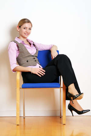 portrait of a successful young woman sitting on a chair photo