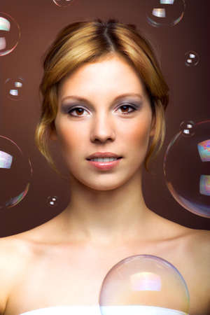 Beauty portrait of a young woman with soap bubbles