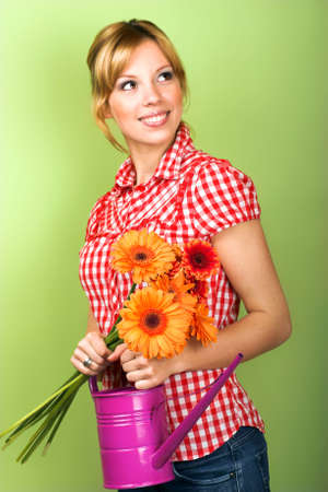 beautiful young woman with flowers and a watering can Stock Photo - 5051869