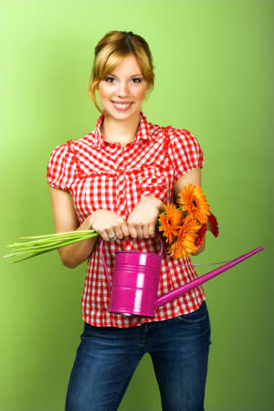 beautiful young woman with flowers and a watering can Stock Photo
