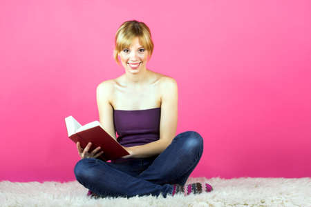 a young beautiful woman is reading on a carpet