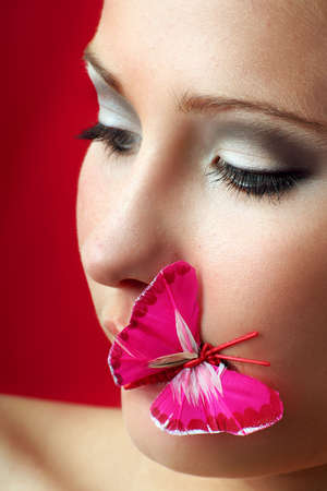 beauty portrait of a beautiful young woman with a butterfly on her mouth