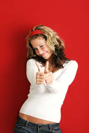 A young, attractive and happy woman is smiling with the thumb up Stock Photo