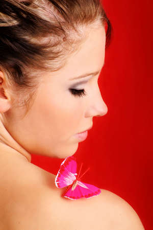 beauty portrait of a beautiful young woman with a butterfly on her shoulder Stock Photo