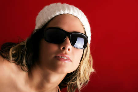 portrait of a beautiful woman with a cap and some sunglasses against red background photo