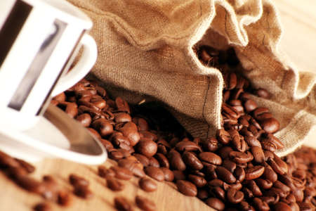 some coffee beans and a jute sack behind a cup of black coffee Stock Photo - 5085526