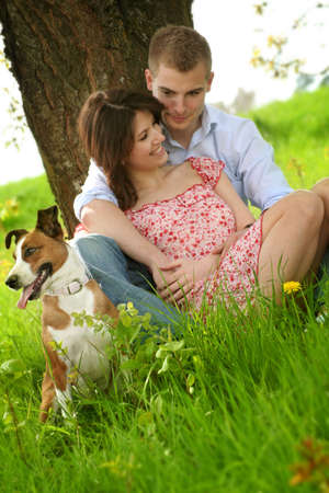 a happy couple is sitting on a green meadow with a dog Stock Photo