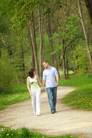 young and happy couple taking a walk in a park photo