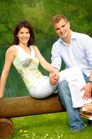 happy and smiling couple sitting on a bank in front of a lake photo