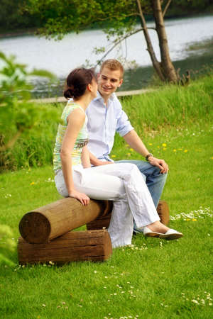 lake flowers: happy and smiling couple sitting on a bank in front of a lake