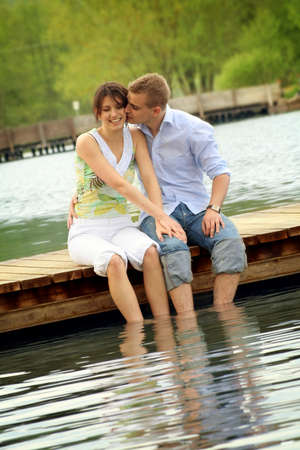 happy and smiling couple sitting on a bridge in front of a lake Stock Photo