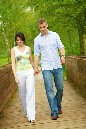 young and happy couple taking a walk on a bridge photo