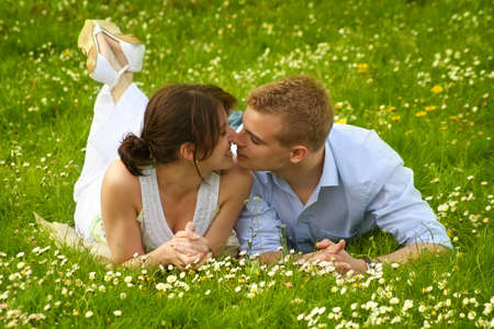 a happy couple on a green meadow is smiling photo