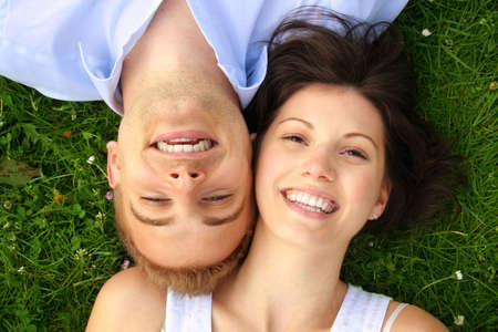 a happy and smiling couple is cuddle on a green meadow Stock Photo