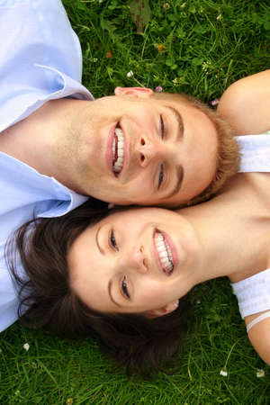 a happy and smiling couple is cuddle on a green meadow photo