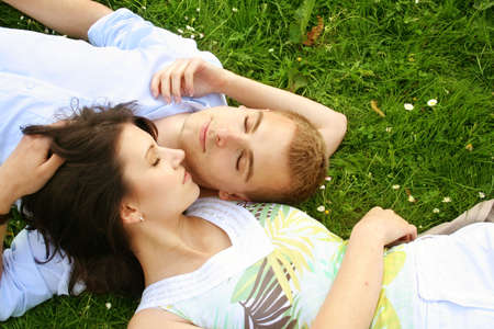 a happy young couple is cuddle on a green meadow photo