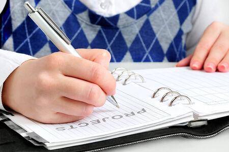 Girl student writing on agenda photo