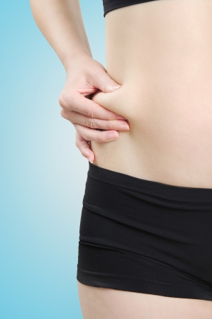 pinches: Woman pinches fat on belly Stock Photo