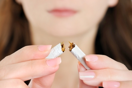 Young woman breaking cigarette on background