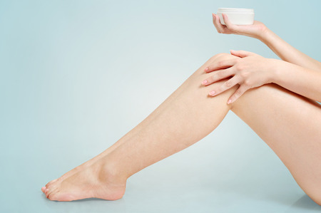 Woman applying cream on feet photo