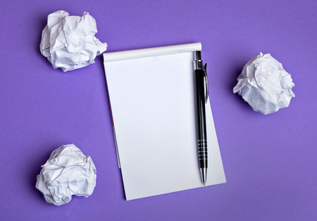 Crumpled paper and notepad on background