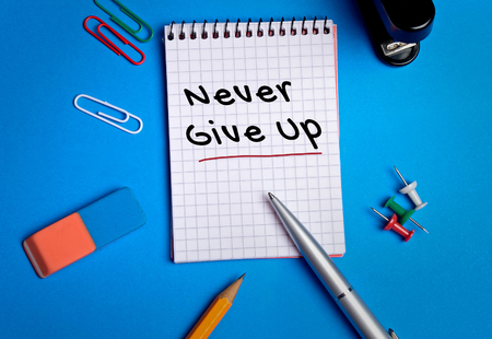 give up: Never Give Up word on notebook page