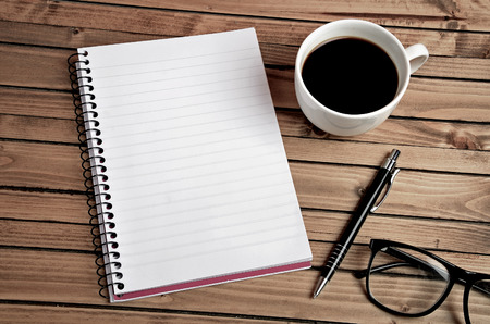 Cup of coffee and notepad on table Standard-Bild