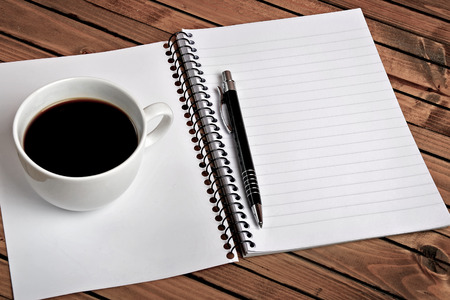 Notepad with coffee cup on table photo