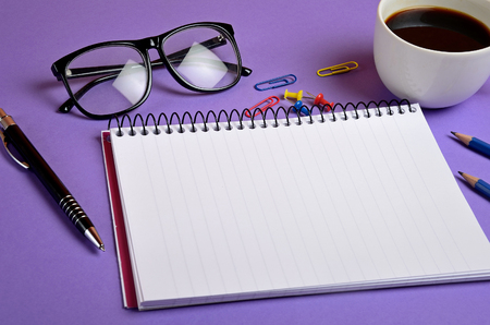 background purple: Empty notebook and office supplies
